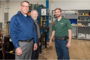Three men in the Greenville repair center grand opening